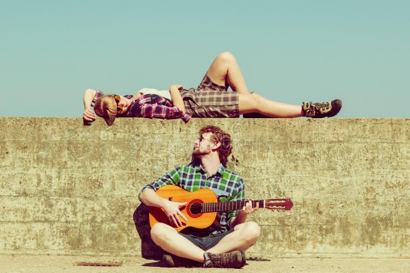 Ung man som spelar gitarren till hans flickvän vid sjösidan royaltyfri fotografi