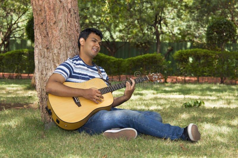Ung man som spelar gitarren under träd fotografering för bildbyråer