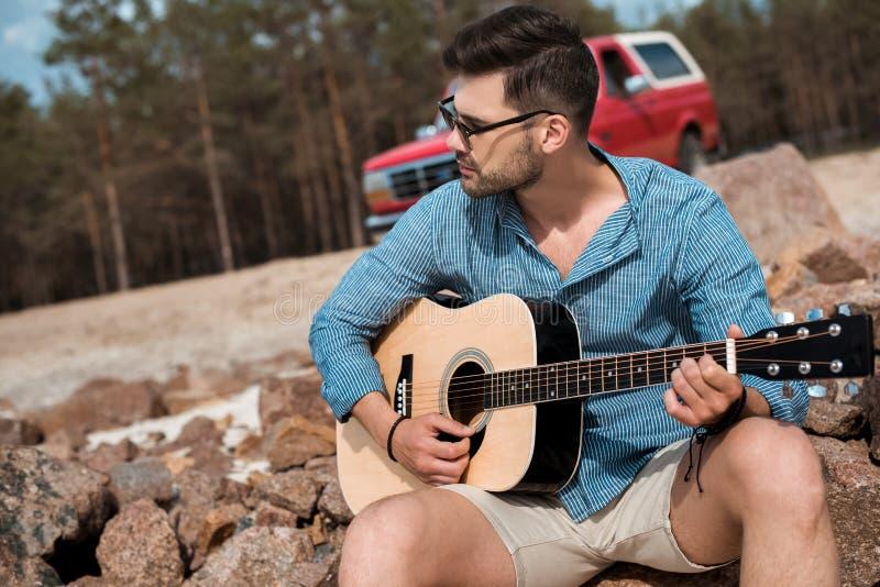 ung man som spelar jeepen för det fria för akustisk gitarr den röda royaltyfria foton