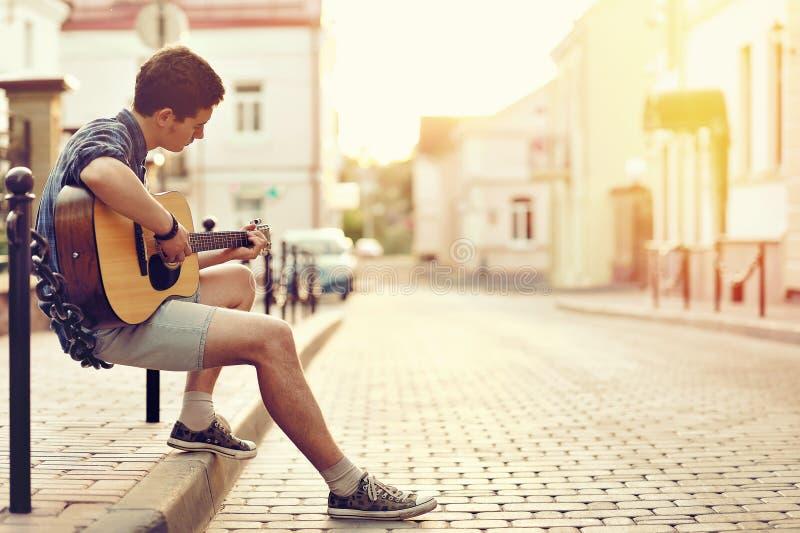 Ung man som spelar på den utomhus- akustiska gitarren - royaltyfria bilder