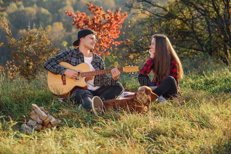 Ung man som spelar på gitarren för hans älskvärda flickvän Lyckliga par med gitarren som vilar på picknick i vår, parkerar royaltyfria bilder