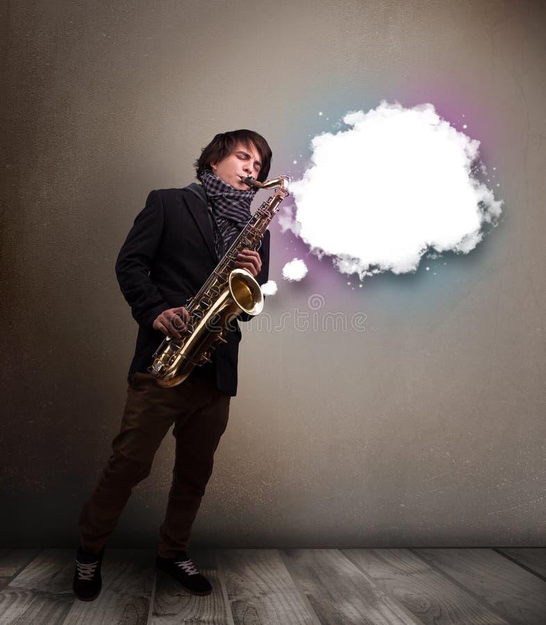 Ung man som spelar på saxofonen med kopieringsutrymme i det vita molnet arkivbild