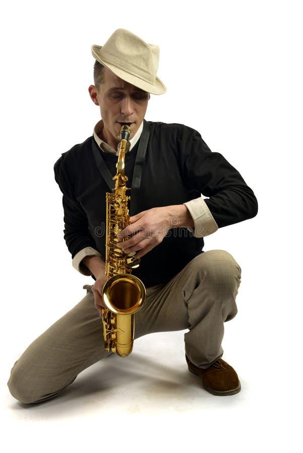 Ung man som spelar saxofonen royaltyfri foto
