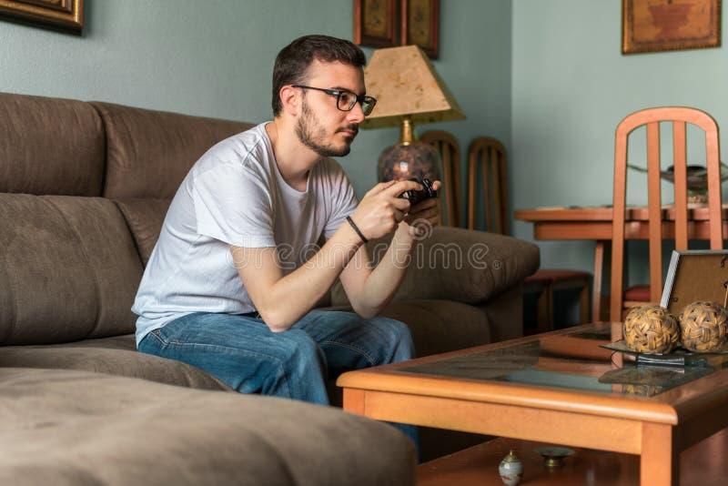 Ung man som spelar videospelet som rymmer den trådlösa kontrollanten arkivfoton