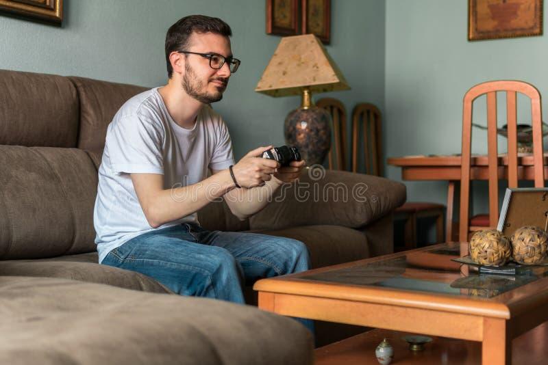 Ung man som spelar videospelet som rymmer den trådlösa kontrollanten royaltyfri fotografi