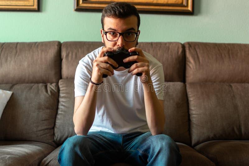 Ung man som spelar videospelet som rymmer den trådlösa kontrollanten fotografering för bildbyråer