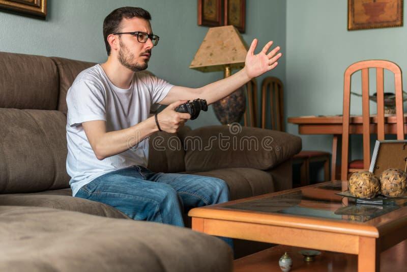Ung man som spelar videospelet som rymmer den trådlösa kontrollanten royaltyfri bild