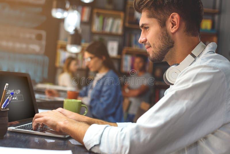 Ung man som spenderar tid i coffee shop royaltyfri bild