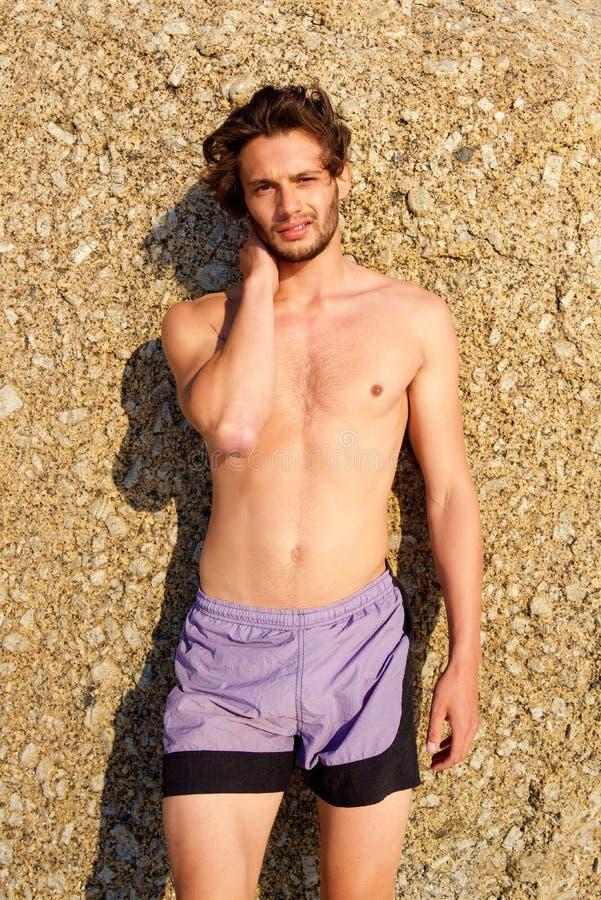 Ung man som står den shirtless yttersidan royaltyfri foto