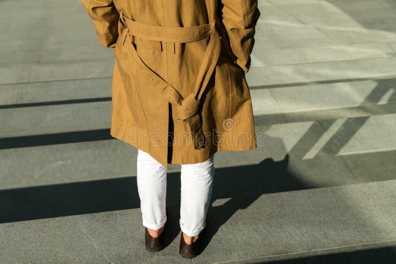 Ung man som står utomhus- och bärande trendigt brunt omslag royaltyfria foton
