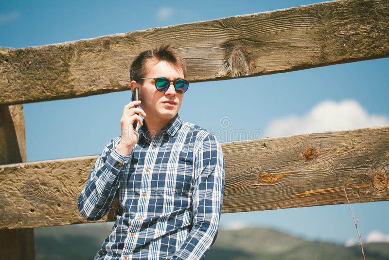 Ung man som stannar till telefonen i bygden royaltyfria bilder