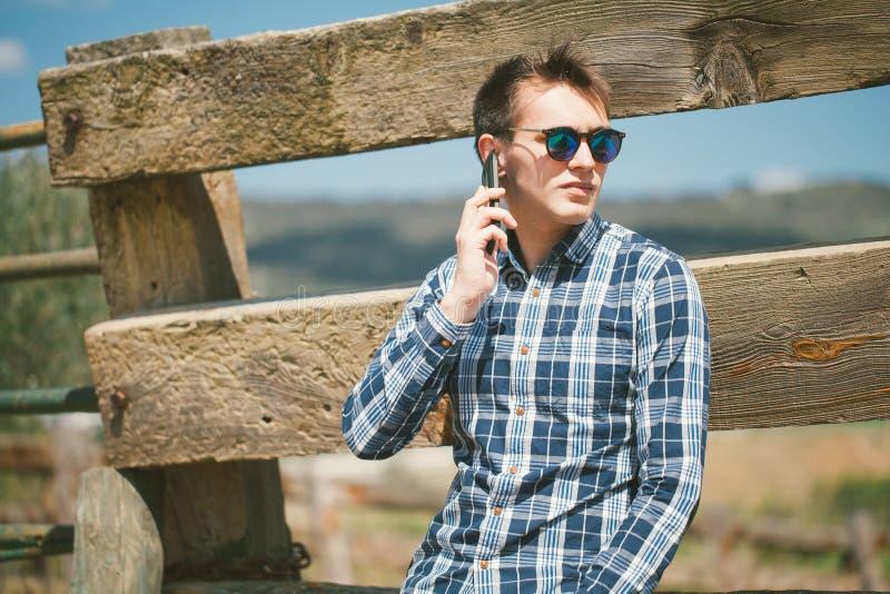 Ung man som stannar till telefonen i bygden royaltyfria foton