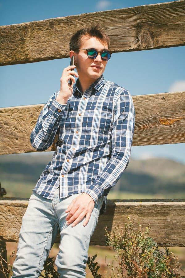 Ung man som stannar till telefonen i bygden fotografering för bildbyråer