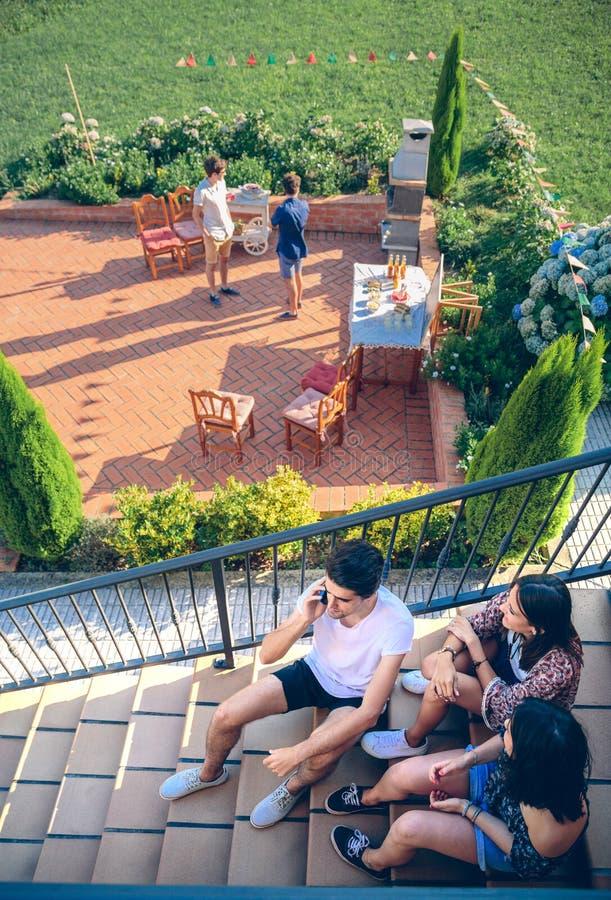 Ung man som stannar till telefonsammanträde på hem- trappa fotografering för bildbyråer