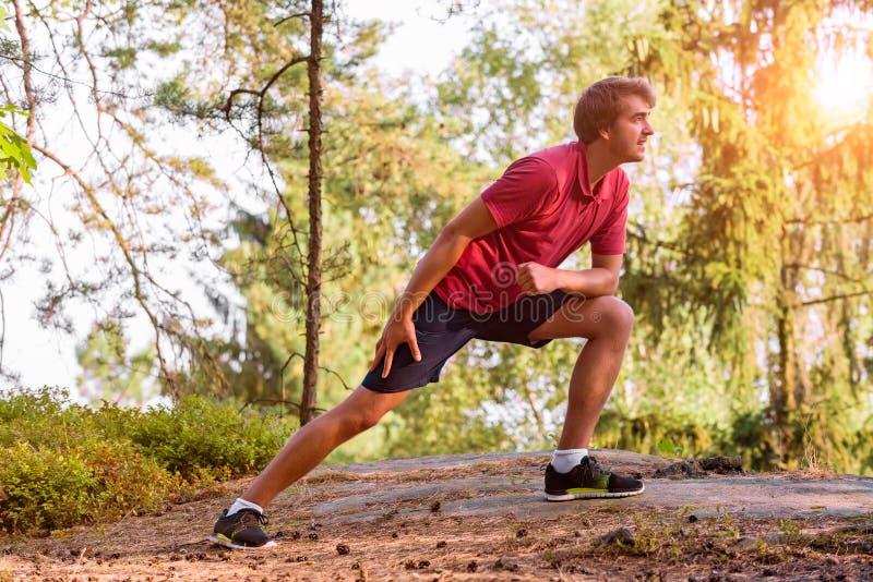 Ung man som sträcker, innan att jogga royaltyfri foto