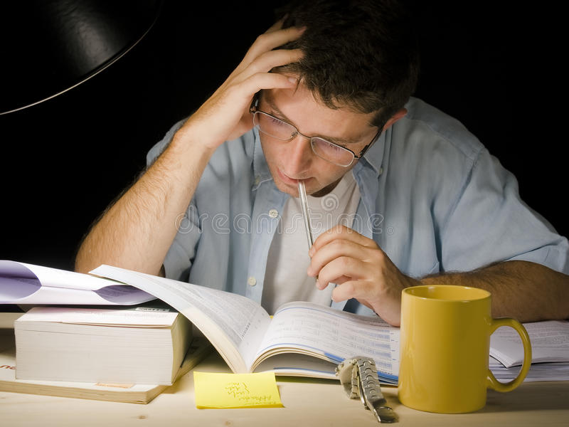 Ung man som studerar på natten royaltyfri bild