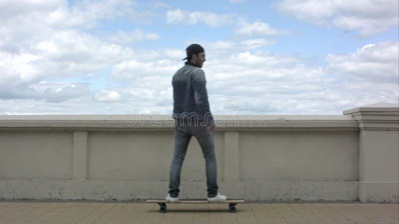 Ung man som syns i ramen och rider en skateboard i molnig dag royaltyfri bild