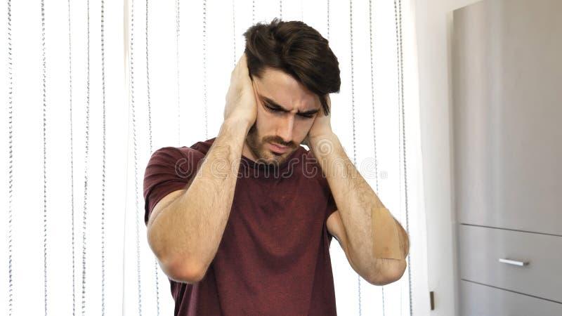 Ung man som täcker hans öron, för mycket oväsen arkivbild