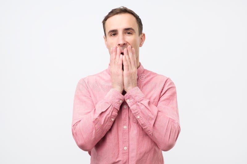 Ung man som täcker hans mun med chockat eller förvånat med rykten royaltyfri bild