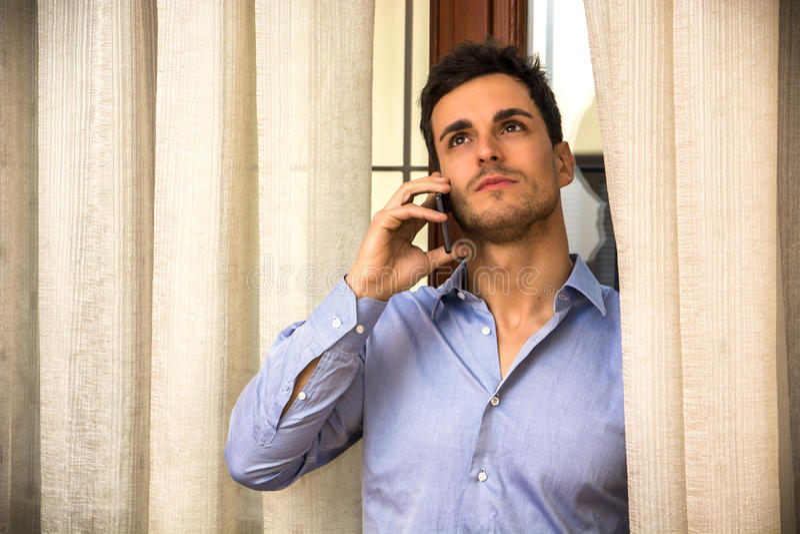 Ung man som talar på telefonen bredvid gardiner royaltyfri bild