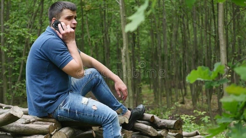Ung man som talar på telefonen i skogsmarken arkivfoto