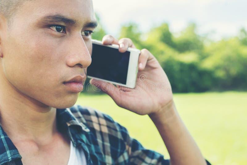 Ung man som talar på telefonen och anseendet på gräset i arkivbild