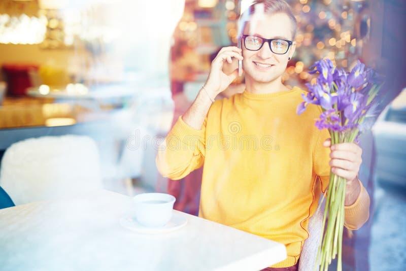 Ung man som talar vid telefonen på datum i kafé arkivbild