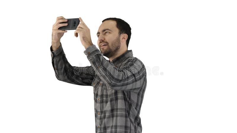 Ung man som tar en selfie på vit bakgrund fotografering för bildbyråer