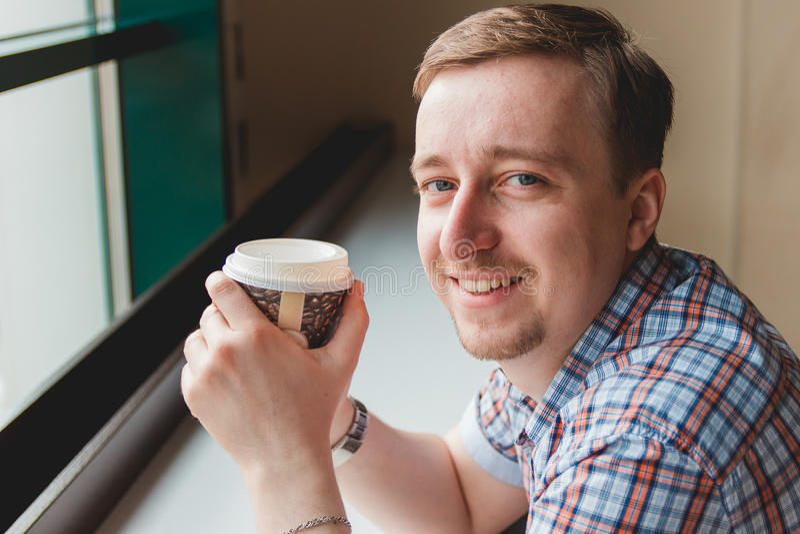 Ung man som tar ett kaffeavbrott på kafét arkivbild