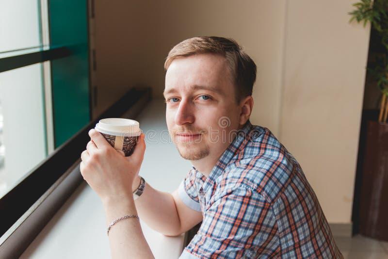 Ung man som tar ett kaffeavbrott på kafét arkivfoton