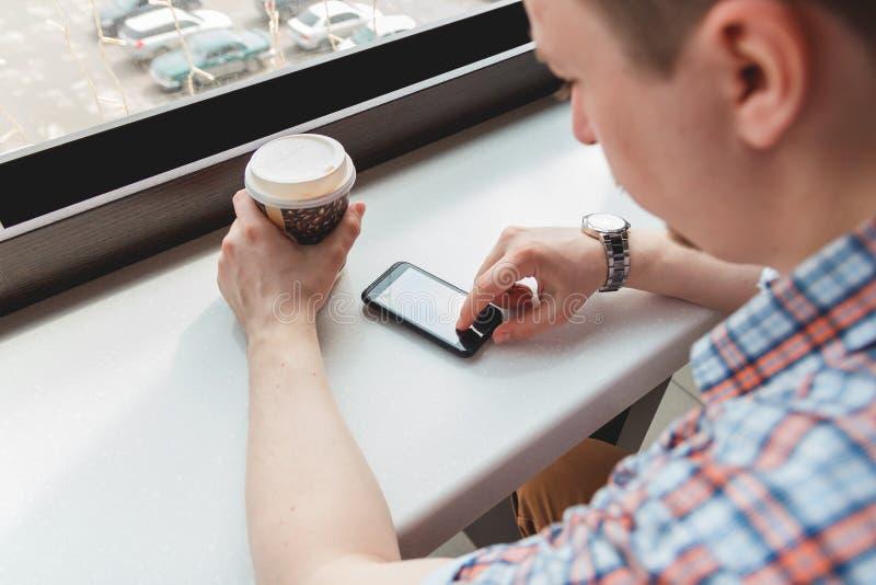 Ung man som tar ett kaffeavbrott på kafét fotografering för bildbyråer