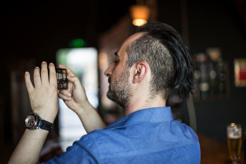 Ung man som tar foto med hans mobiltelefon i stången arkivfoto