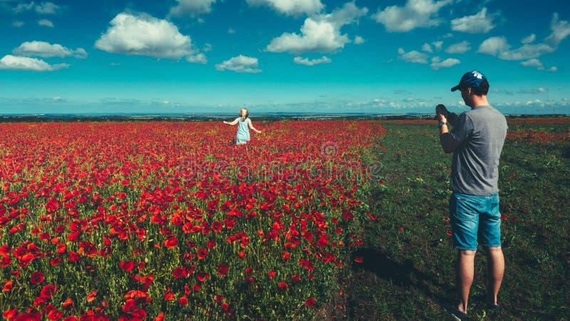 Ung man som tar foto på smartphonen, ung flicka som stöter ihop med fältet av röda vallmo, reslustturismbegrepp arkivbild