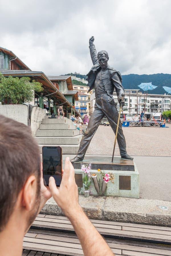 Ung man som tar fotoet av den berömda Freddie Mercury statyn på marknadsfyrkanten som vänder mot sjöGenèvegummilacka Leman i Mont royaltyfria foton