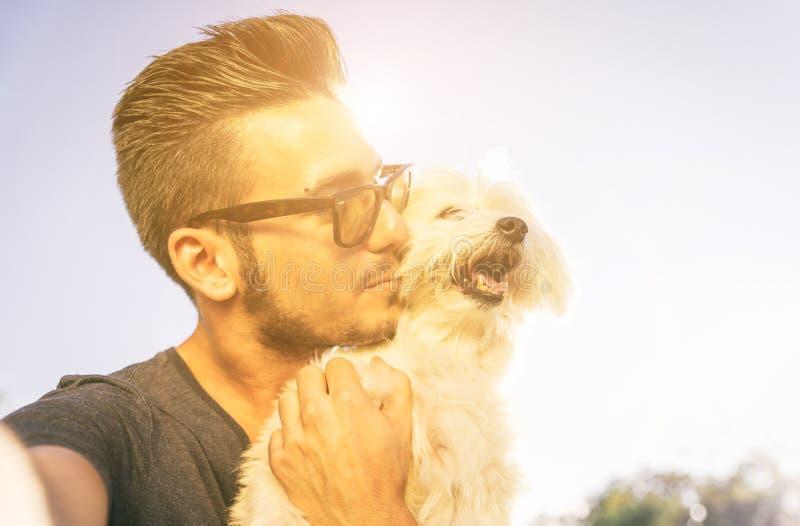 Ung man som tar selfie med hans utomhus- gulliga hund fotografering för bildbyråer