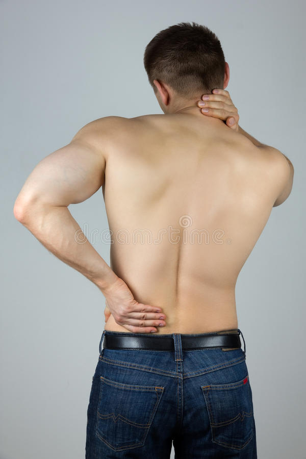 Ung man som trycker på hans baksida och hals för smärta royaltyfria bilder