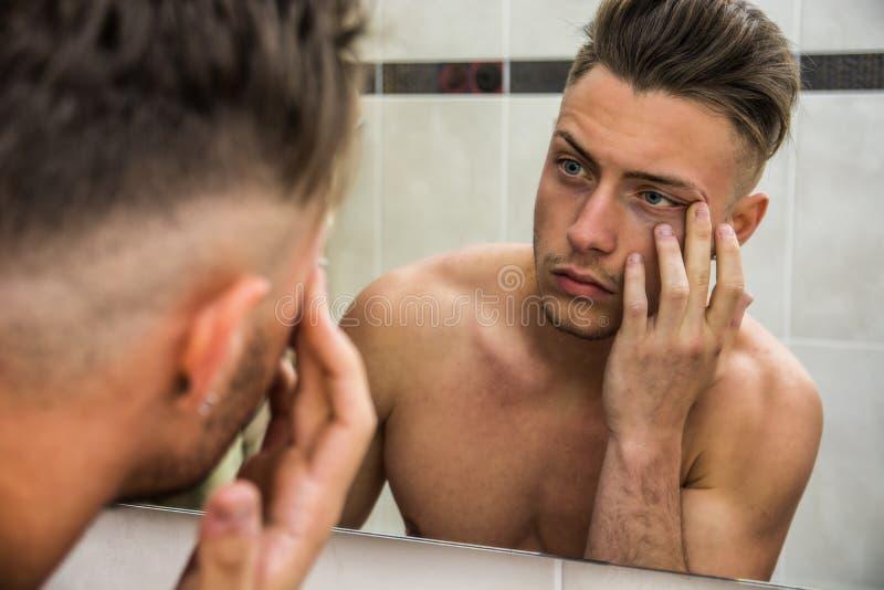 Ung man som trycker på hans framsida, medan se i spegel royaltyfria foton