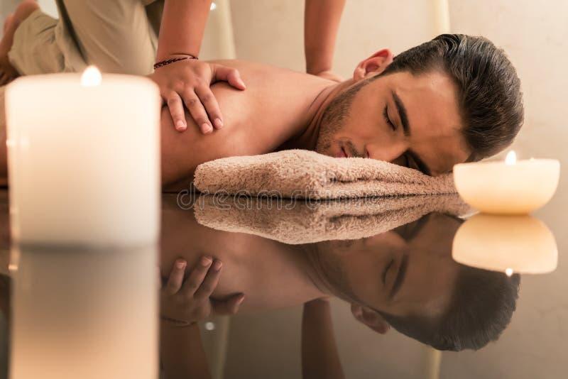 Ung man som tycker om de läka fördelarna av den traditionella thailändska massagen arkivfoto