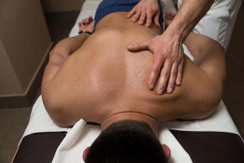 Ung man som tycker om en massage arkivfoton