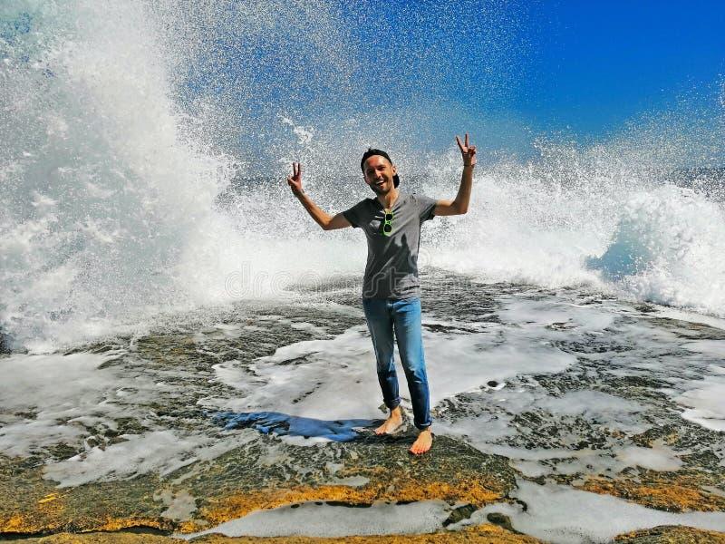 Ung man som tycker om höga vågor med vattenvågor med färgstänk royaltyfri bild