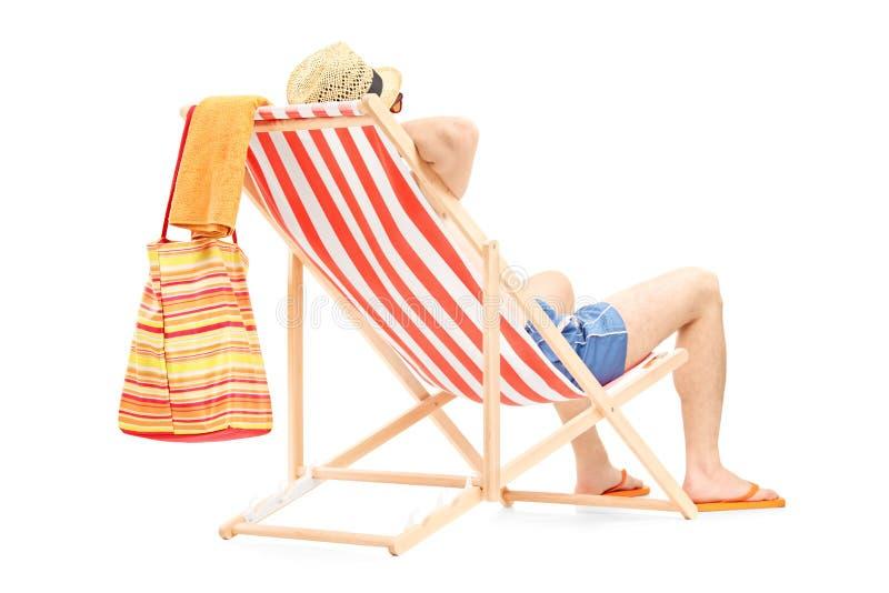 Ung man som tycker om på en strandstol royaltyfri foto