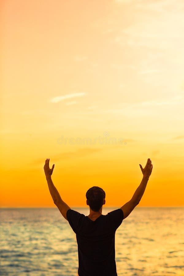 Ung man som tycker om solnedgången med hans armar i luften Lyckligt och fritt arkivbild