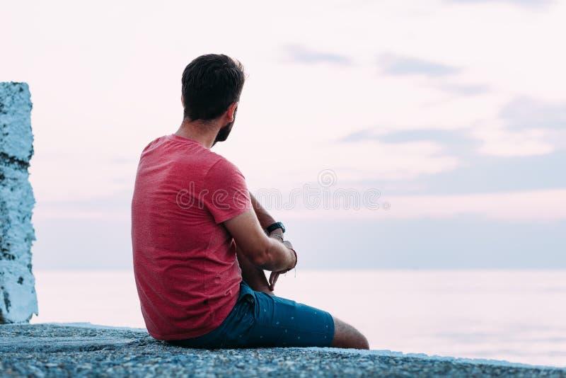 Ung man som tycker om vid havet royaltyfria foton