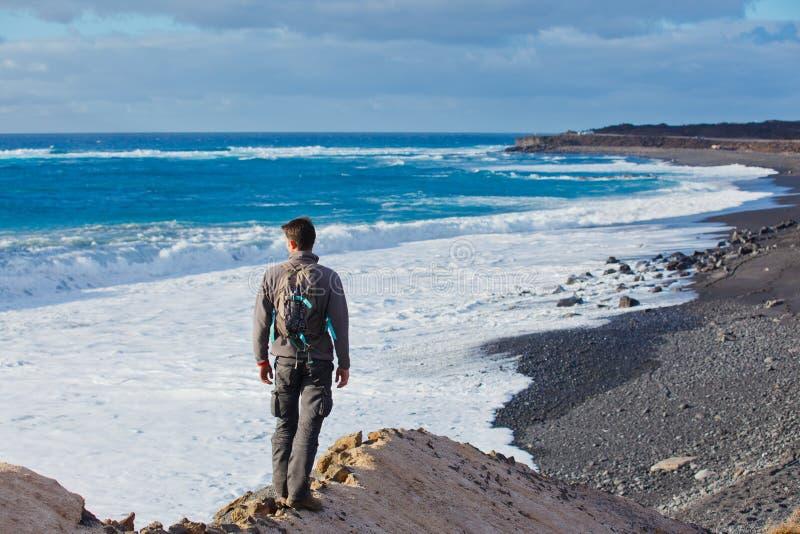 Ung man som upp till fotvandrar och ser havet arkivfoton