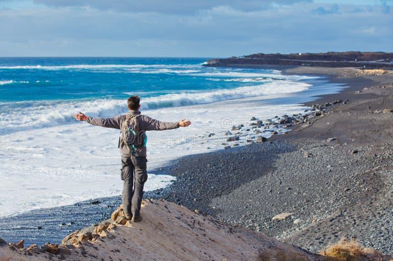 Ung man som upp till fotvandrar och ser havet royaltyfri bild