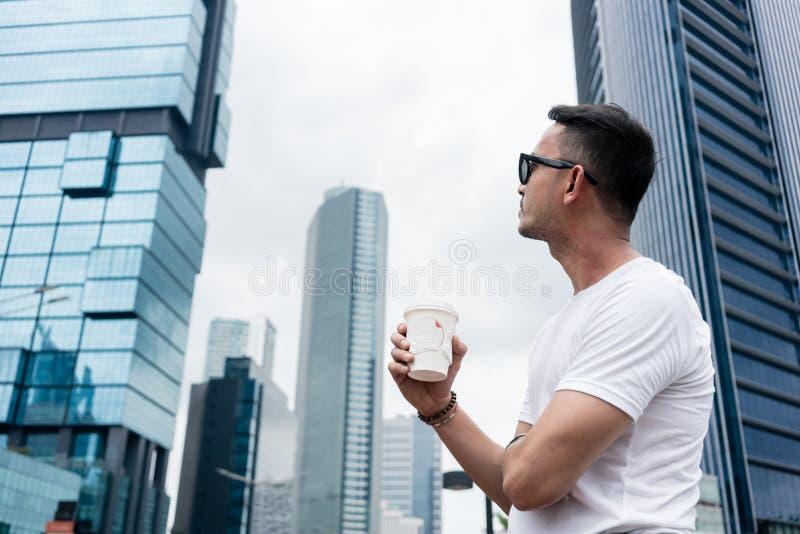 Ung man som upp till ser skyskraporna av en modern affär dis royaltyfri foto