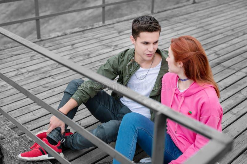 Ung man som uppmärksamt ser på hans flickvän och har viktigt samtal arkivbild