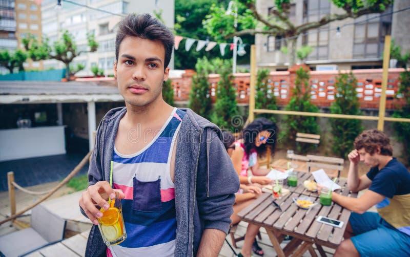 Ung man som utomhus dricker den ingav vattencoctailen royaltyfri fotografi