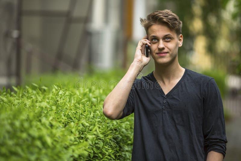 Ung man som utomhus talar på mobiltelefonen tryst royaltyfri fotografi