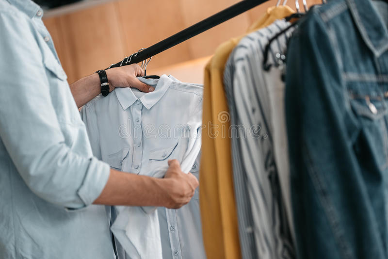 Ung man som väljer trendiga skjortor i boutique royaltyfri fotografi